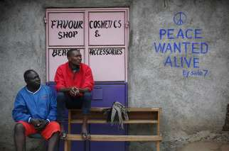 Men sit in front of a wall with a message of peace July 23 in Nairobi, Kenya. Kenyan Catholic bishops have urged citizens to prepare to vote peacefully in the Aug. 8 general elections.