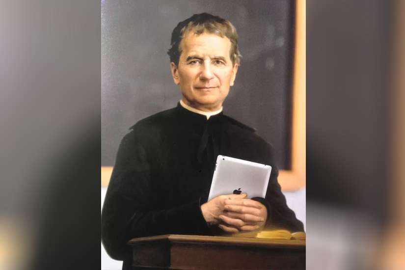 Image of St. John Bosco with an iPad depicts his zeal for evangelization by using every means of communication available.