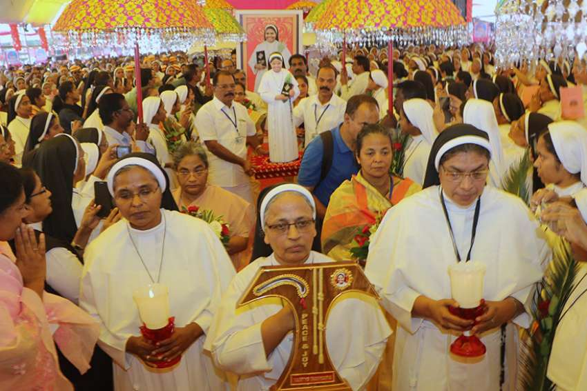 Sister Anne Joseph, superior general of the Franciscan Clarist order, carries the relic of Blessed Rani Maria Vattali during her Nov. 4 beatification Mass in Indore, India. At right is Sister Selmy Paul, younger sibling of Blessed Rani Maria, who was killed in 1995.