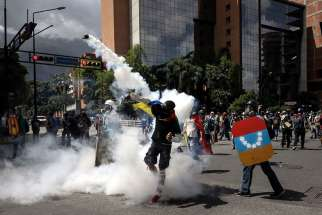 Opposition protesters clash with Venezuelan government forces June 22 in Caracas. A Venezuelan military police sergeant fatally shot a protester who was attacking the perimeter of an airbase, the interior minister said, bringing renewed scrutiny of the force used to control riots that have killed at least 76 people.