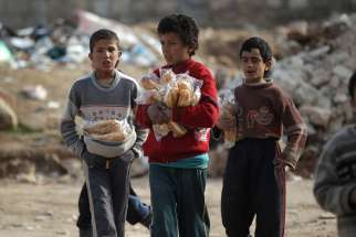Boys carry sandwiches Jan. 20 in Aleppo, Syria. Conveying Pope Francis' closeness to the Syrian people, a Vatican delegation visited Aleppo Jan. 18-23 following the end of the hostilities that left thousands dead and the city in ruins.