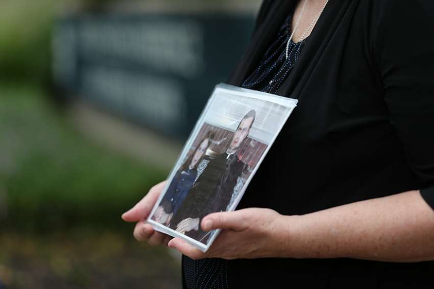 Becky Ianni, who is the Washington and Virginia director of the Survivors Network of those Abused by Priests, or SNAP, holds a photo of herself as a child with a priest Aug. 21 outside the headquarters of U.S. Conference of Catholic Bishops in Washington. Lanni was allegedly abused by the priest in the photo.