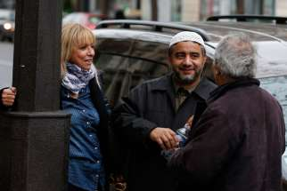 Abdelali Mamoun, an imam in Paris, talks with people on the street near the Bataclan music hall in Paris Nov. 16. About a dozen imams in the city showed up at a memorial near Bataclan, where about 100 people were killed in the Nov. 13 terrorist attacks by the Islamic State.