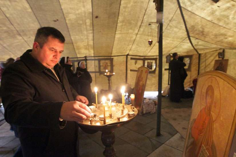 A man lights a candle in a temporary Ukrainian Catholic tent church in 2013 during anti-government protests in Kiev. Archbishop Sviatoslav Shevchuk of Kiev-Halych and other Ukrainian Catholic leaders have warned their church is being driven underground a gain, a quarter-century after it was re-legalized with the end of communist rule.