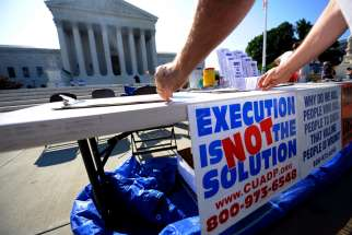 A member of the Abolition Action Committee hangs a sign in front of the Supreme Court in Washington during a 2008 vigil to abolish the death penalty.
