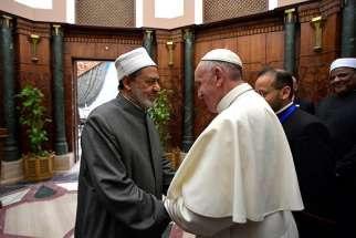 Sheik Ahmad el-Tayeb, grand imam of al-Azhar University, greets Pope Francis at a conference on international peace in Cairo April 28.