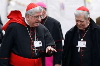 Cardinals Thomas Collins of Toronto and Jorge Urosa Savino of Caracas, Venezuela, talk as they arrive for a session of the Synod of Bishops on the family at the Vatican Oct. 14.