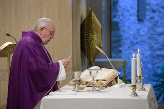 Pope Francis holds the Eucharist during morning Mass in the chapel of his residence, the Domus Sanctae Marthae, at the Vatican April 9, 2019. The pope said the devil targets those who succumb to despair and negativity.