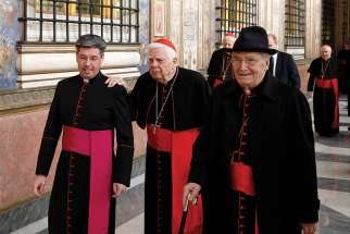 Late Cardinal Bernard F. Law and Cardinal Agostino Cacciavillan (right), former apostolic nuncio to the United States, leave after Pope Francis' audience with members of the Roman Curia in Clementine Hall at the Vatican Dec. 22, 2014.