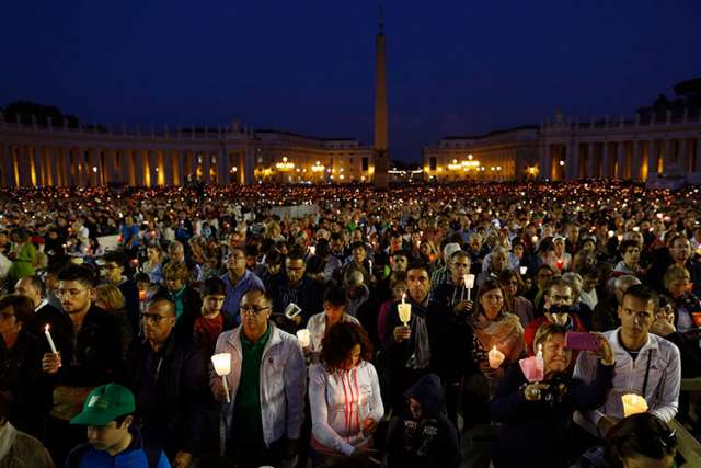 "People attend an Oct. 4 prayer vigil led by Pope Francis for the extraordinary Synod of Bishops on the family in St. Peter's Square at the Vatican. The pope called for ""sincere, open and fraternal"" debate during the two-week long synod, which opened Oct. 5."