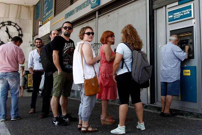People queue to withdraw money from an ATM outside a branch of Greece's National Bank in Athens, Greece, July 6.