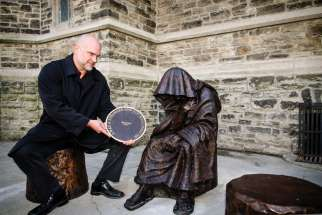 Catholic sculptor Timothy Schmalz sits next to his recently unveiled statue, When I Was a Stranger, at Toronto's St. Paul's Anglican Church.