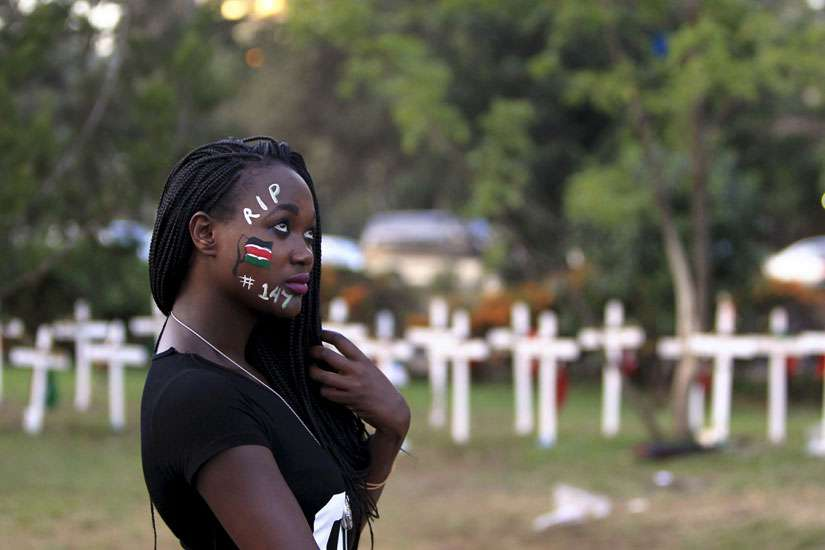 "A student wearing face paint walks past wooden crosses during an April 14 memorial concert in Nairobi, Kenya, for the 147 people killed in an attack on Garissa University College. Pope Francis is calling for perpetrators of extremist violence in Kenya ""t o come to their senses and seek mercy."""