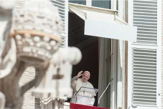 Pope Francis greets the crowd from the window of his studio overlooking St. Peter's Square as he leads the Angelus at the Vatican Oct. 4, 2020.