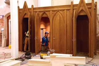 A workman completes the installation of one of the cathedral's new confessionals.