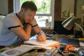 "Catholic cartoonist Ben Hatke sketches his character ""Zita the Spacegirl"" in a studio in his Front Royal, Va., home May 17. His graphic novel series features a character who was named in honour of St. Zita."