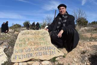 "Bishop Oscar Cantu of Las Cruces, N.M., kneels by a stone that reads ""We Refuse To Be Enemies"" Jan. 16 at the entrance to the Tent of Nations in the West Bank, near Bethlehem. Thirteen bishops from Europe and North America visited the area as part of the Holy Land Coordination."