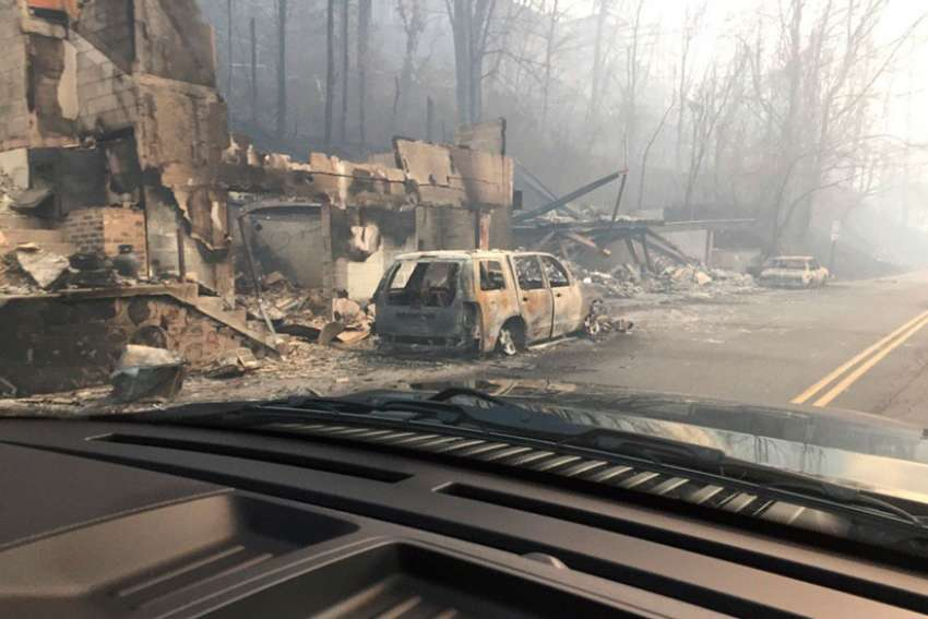 Burned buildings and cars are seen Dec. 1 in Gatlinburg, Tenn., in the aftermath of wildfires. Raging wildfires fueled by high winds claimed the lives of at least seven people, forced the evacuation of thousands, including Father Antony Punnackal of St. Mary's Church, and damaged hundreds of buildings in the popular mountain resort town.