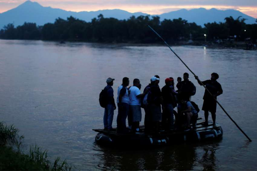Residents of Tecun Uman, Guatemala, and migrants from Central America cross the Suchiate River June 10, 2019, to enter Ciudad Hidalgo, Mexico. The Mexican bishops' conference questioned details of the U.S.-Mexico immigration deal, in which Mexico will strengthen security along its southern border with Guatemala and impede the path of migrants fleeing poverty, violence and food insecurity.