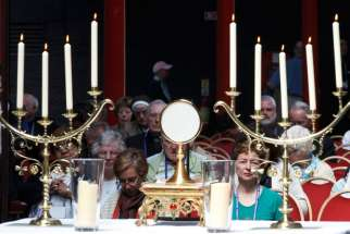 People adore the Eucharist during Mass.