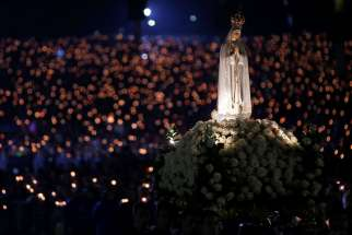 A statue of Our Lady of Fatima is carried through the crowd at the Marian shrine of Fatima in central Portugal. Thousands of pilgrims visit the shrine each year. Lucia dos Santos and her cousins, Francisco and Jacinta Marto, received the first of several visions May 13, 1917.