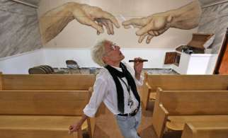 "Bill Levin poses in the sanctuary at The First Church of Cannabis, on June 23, 2015. The sanctuary, still under renovation, includes a painting on the back wall of two hands passing a cannabis cigarette. The painting, by CS Stanley, the church's minister of art, is similar to a detail of the Michelangelo ""Creation of Adam"" on the Sistine Chapel ceiling."