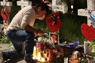 Jose Louis Morales cries as he kneels June 21 at a makeshift memorial for his brother Edward Sotomayor Jr. and other victims of the Pulse night club shootings in Orlando, Fla. Msgr. Stephen Rossetti, a Washington-based licensed psychologist, plans to conduct a free webinar in late August to prepare priests, religious and other church members how to deal with the trauma that follows large-scale tragedies.