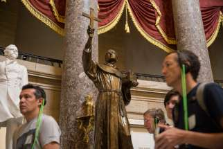 Tourists walk past a statue of Blessed Junipero Serra in Statuary Hall on Capitol Hill in Washington Sept. 21. Pope Francis celebrated a Mass of canonization for Blessed Junipero Serra Sept. 23 outside the Basilica of the National Shrine of the Immaculate Conception in Washington.