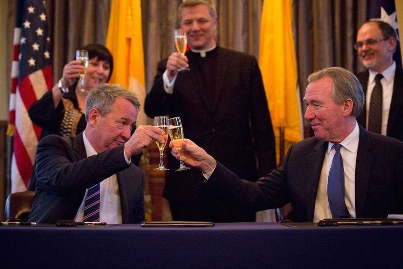 John Garvey, right, president of The Catholic University of America, toasts Greg Craven, vice chancellor of Australian Catholic University, in Washington Jan. 29 after they signed a memorandum of understanding for their universities' new Rome Center.