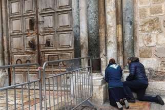 "Tourists pray outside the locked doors of the Church of the Holy Sepulchre Feb. 26 in Jerusalem's Old City. Protesting several recent actions they described as a ""systematic campaign against the churches and the Christian community in the Holy Land,"" the heads of Christian churches announced Feb. 25 they were closing of the doors of the church."