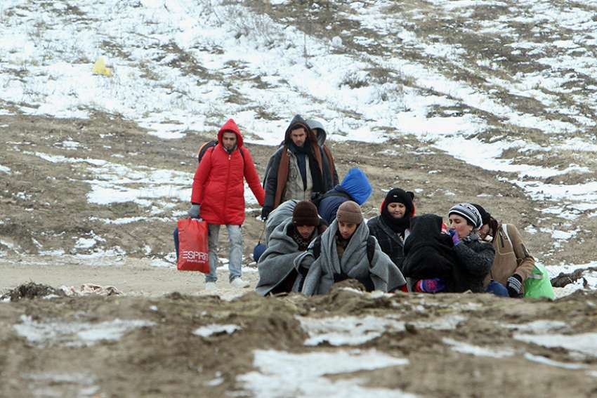 A group of migrants from Syria, Iraq and Afghanistan, on their way to seek asylum in Germany or Austria, walk Jan. 24 along the frozen route from the border between Serbia and Macedonia to a temporary camp for migrants Jan. 2016.