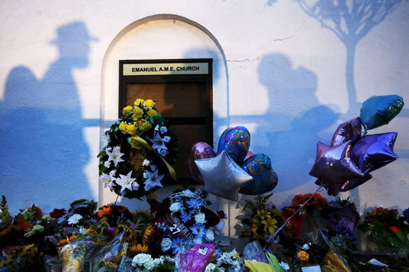 Mourners cast shadows on the wall of a makeshift memorial at the Emanuel African Methodist Episcopal Church in Charleston, S.C., June 18. Nine people were murdered the day before during a Bible study session at the church.