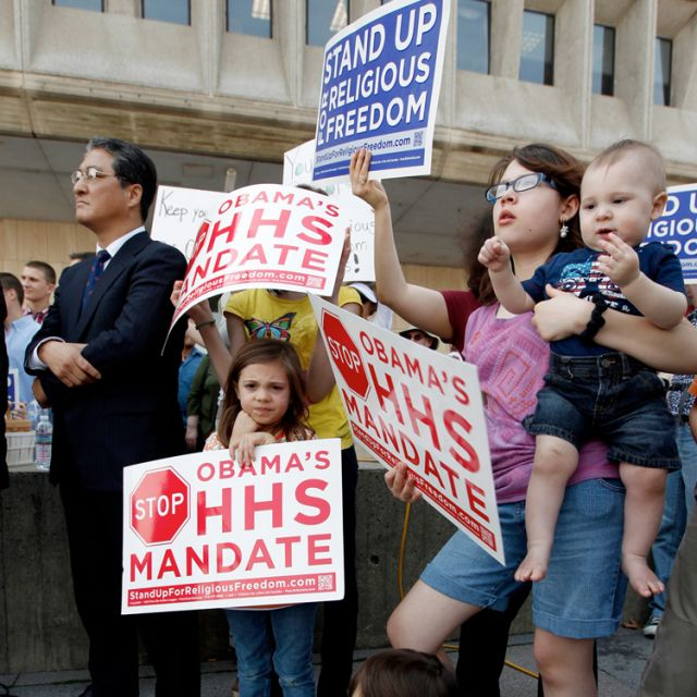 People rally in March outside the Department of Health and Human Services in Washington against the government mandate that would require nearly all employers to cover contraceptives and sterilization in their health plans. Forty-three Catholic dioceses, schools, hospitals, social service agencies and other institutions filed suit in federal court May 21 to stop three government agencies from implementing the mandate.