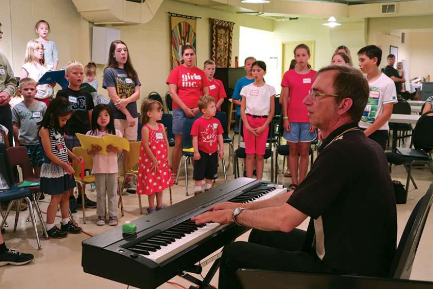 Uwe Lieflander leads a warm up exercise with Sparrows from Immaculate Conception Parish in Port Perry, Ont.