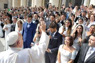 Pope Francis greets newly married couples during his general audience in St. Peter's Square at the Vatican Sept. 30, 2015.