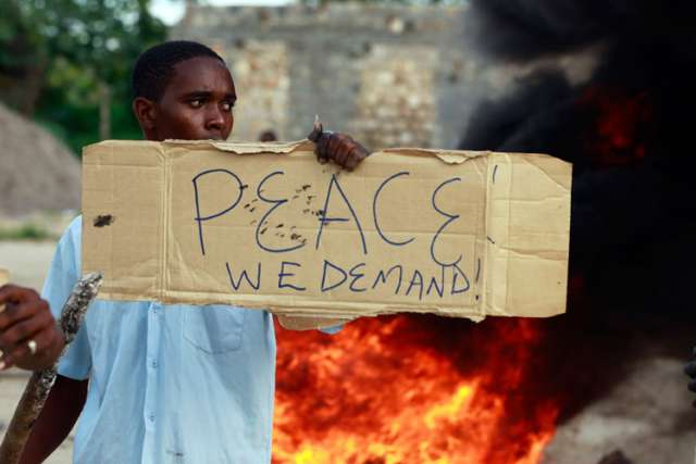 A resident holds a placard as he participates in a June 17 protest against the recent attack by unidentified gunmen in the town of Mpeketoni, Kenya. Nearly 50 people were killed and others wounded when more than two dozen unidentified gunmen attacked the coastal town.