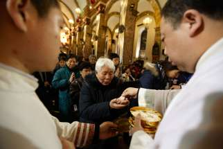 Chinese Catholics receive Communion in 2012 during Christmas Eve Mass in Beijing. A top Politburo official told faith leaders that religious groups must promote Chinese culture and become more compatible with socialism.