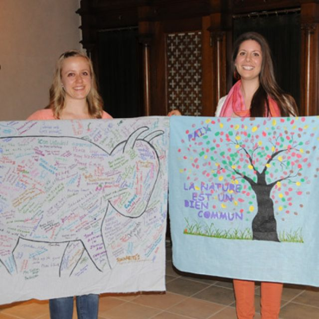 Barbara Gajda, left and Janelle de Rocquigny stand with solidarity banners before departing for Rio de Janeiro. The banner on the left was signed by D&P Manitoba members at St. Ignatius parish and St. Boniface Cathedral and the banner on the right was painted by the youth of St. Boniface Cathedral.