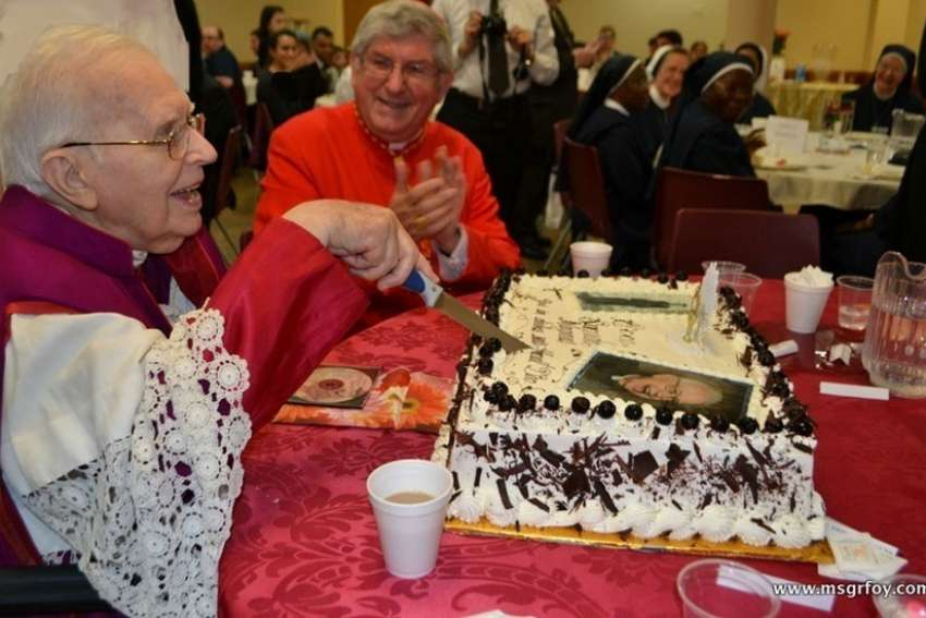 Msgr. Vincent Foy cuts the cake for his 100th birthday celebration with Cardinal Thomas Collins sharing the moment. Msgr. Foy died at the age of 101 March 13.