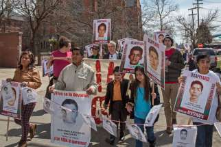 Demonstrators rally outside St. Anne's Catholic Church in Detroit to protest the September 2014 disappearance of 43 students from a teachers college in the southern Mexican state of Guerrero. The students from Ayotzinapa Teacher Training College were app arently arrested by local police who handed them over to a drug gang.