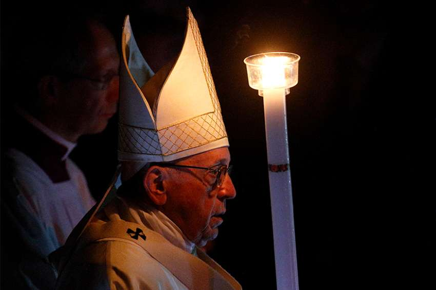 Pope Francis carries a candle as he arrives in procession to celebrate the Easter vigil in St. Peter's Basilica at the Vatican March 31.