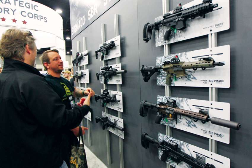 Men view guns during the National Rifle Association's annual meetings and exhibits show in Louisville, Ky, in 2016.
