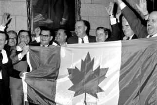 Members of Parliament celebrate with the new flag after the Liberals invoked closure to end the flag debate in the House of Commons.