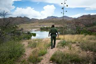 Border Patrol Agent Bryan Flowers walks above Pena Blanca Lake, a small recreation area about 17 miles northwest of Nogales, Ariz., July 16. Because of the water availability, smuggling routes through this region are common, Flowers said.