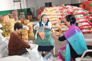 St. Joseph Sister Monique Niraula joins two other women in packing relief material for earthquake victims at Assumption Catholic Church in Lalitpur, Nepal, May 1.