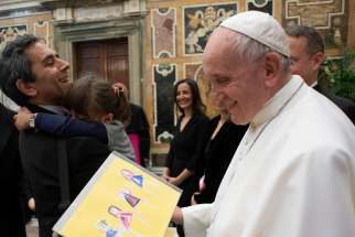 Pope Francis accepts a gift of artwork during an audience with members of the Foreign Press Association of Italy, at the Vatican May 18, 2019.
