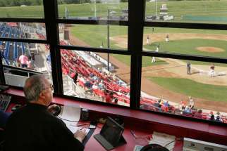 Father Craig Collison, a priest in the Diocese of Sioux City, Iowa, watches baseball action from the announcer's booth June 4 as the Sioux City Explorers play the Gary, Ind., Southshore Railcats. Father Collison, a play-by-play announcer for the minor le ague team, loves baseball and says being at the ballpark in a priest's collar gives him an opportunity to evangelize.