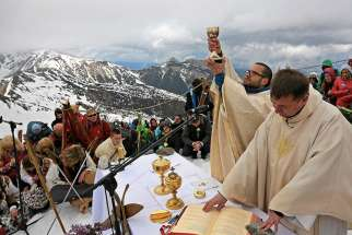 A priest raises the chalice as he celebrates Mass in honor of Sts. John Paul II and John XXIII in the ski resort Kasprowy Wierch in Poland's Tatra Mountains April 27. That day at the Vatican, Pope Francis canonized the two former popes.