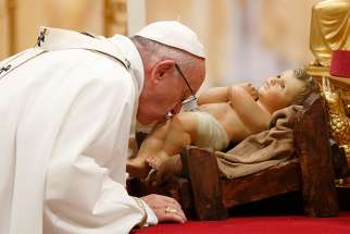 Pope Francis kisses a figurine of the baby Jesus as he celebrates Christmas Eve Mass in St. Peter's Basilica at the Vatican Dec. 24.