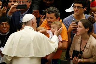 Pope Francis greets a baby during his general audience in Paul VI hall at the Vatican Aug. 1.